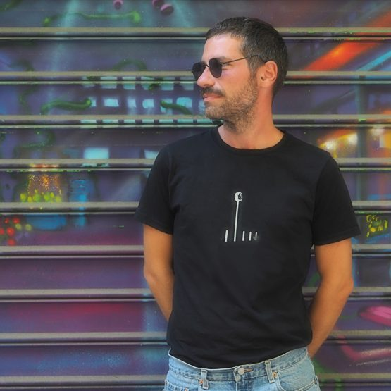 Man standing in front of a graffiti wall wearing a t-shirt made of organic cotton with a design silkscreen printed on it. Unisex