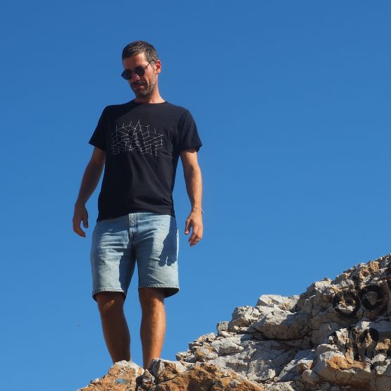 Man standing on the rocks wearing a t-shirt made of organic cotton with a design silkscreen printed on it.