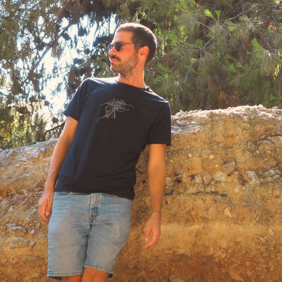 Man standing against the rocks wearing a t-shirt made of organic cotton with a design silkscreen printed on it.