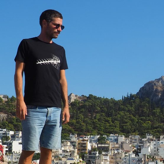 Man standing outside on a hill wearing a t-shirt made of organic cotton with an old tv antenna design silkscreen printed on it.