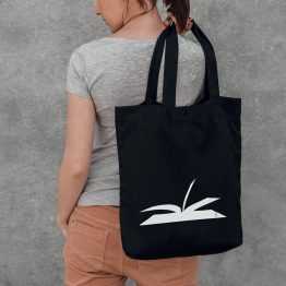 A woman holding on her back a tote bag with an open book cutout design printed on it