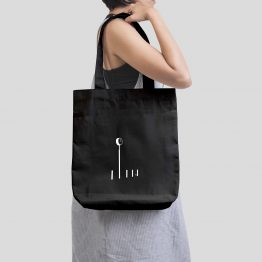 A woman holding a tote bag with a clock on a pole cutout design printed on it.