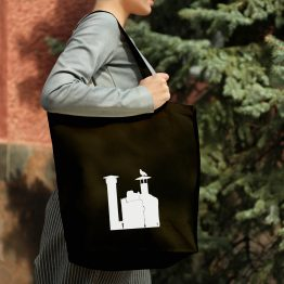 A woman holding a tote bag with a dove sitting on a chimney cutout design printed on it.