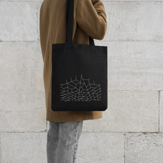 Someone holding a tote bag with a dove sitting on geometrical outlines design printed on it.