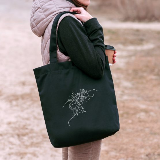 A woman holding a tote bag with an asparagus fern cutout design printed on it.