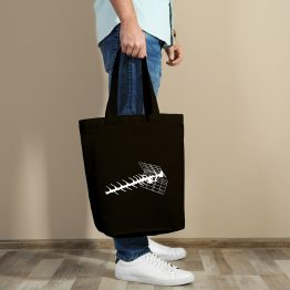 A man holding a tote bag with an old tv antenna cutout design printed on it.
