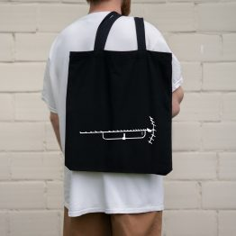 A man holding on his back a tote bag with an old tv antenna cutout design printed on it.