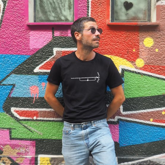 Man standing in front of a graffiti wall wearing a t-shirt made of organic cotton with an old tv antenna design silkscreen printed on it. Unisex