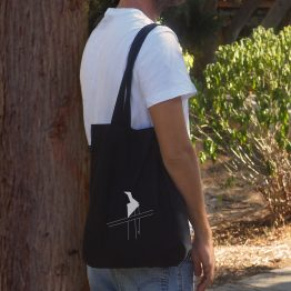 A man walking is holding a tote bag with a cutout design of a weathercock printed on it.
